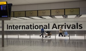 Passengers walk past a sign in the arrivals area at Heathrow Airport in London.