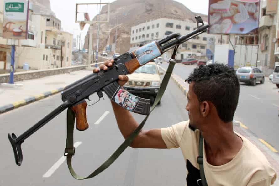 A member of Yemen's southern separatist holds his weapon with a picture of Bridgadier General Muneer al-Yafee, killed in a Houthi missile attack, in Aden.