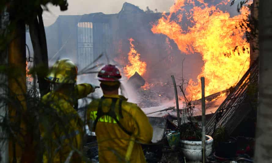 Firefighters put out flames from the South firem which swept through Lytle Creek, California, on Wednesday.