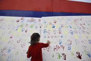 A girl adds her handprint to an art installation during an awareness campaign for missing children.