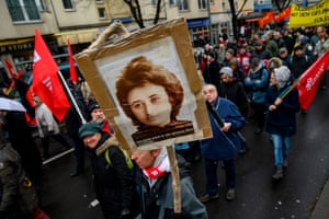 Berlin, Germany: a demonstrator holds a placard featuring a portrait of Communist revolutionary Rosa Luxemburg during a march to the Socialist Monument at Berlin's Friedrichsfelde central cemetery where Luxemburg is buried. Thousands from across the world gathered in Berlin to mark the 100th anniversary of the murder of Luxemburg and Karl Liebknecht