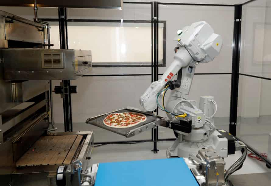 A robot places a pizza into an oven at Zume Pizza in Mountain View, California.