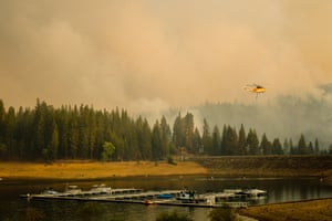 Trees burn near a drought-hit reservoir while a firefighting helicopter flies above a boat dock in the Lake Tahoe basin