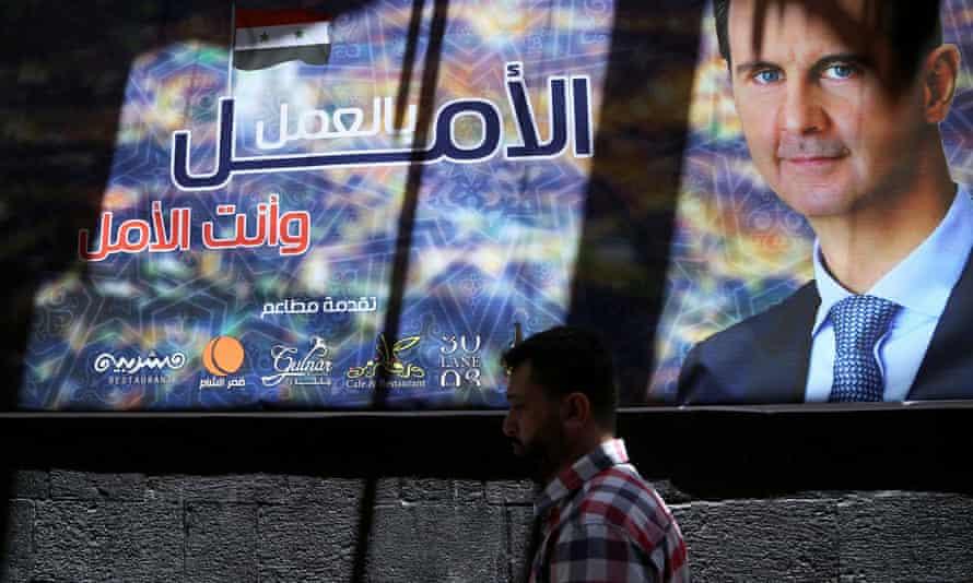 A man walks past a banner depicting Syria's president, Bashar al-Assad, in Damascus