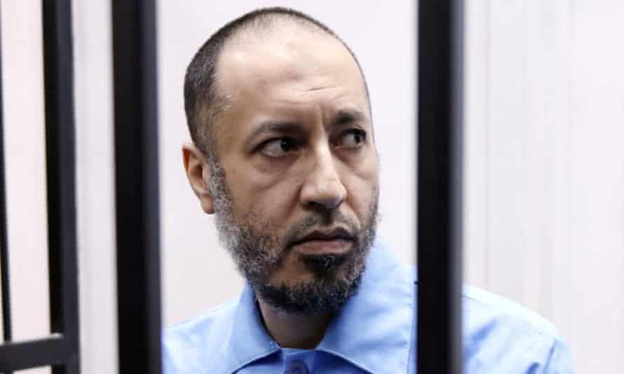 Saadi Gaddafi sits dressed in blue prison clothing