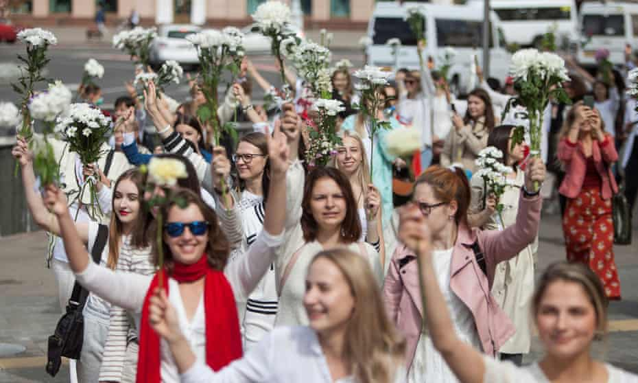 Women wearing white and waving flowers take part in a procession against police violence in Minsk.