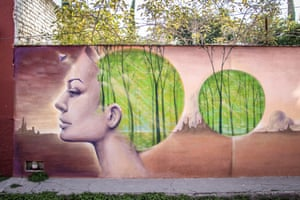 """Wall mural showing a woman's face where the hair on her head has been replaced by a painting of trees in a forest. Comment by photographer: """"San Miguel de Allende is another beautiful colonial town known for its thriving arts. There are murals throughout the streets, like this one which was outside my hotel."""""""