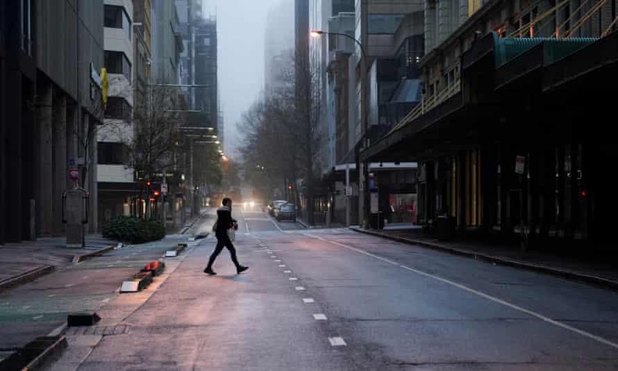 man walks across empty street