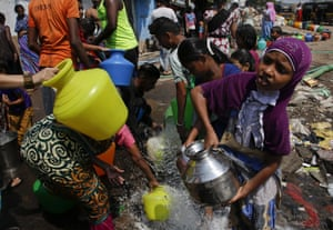 People collect water from a construction site at a slum area in Mumbai