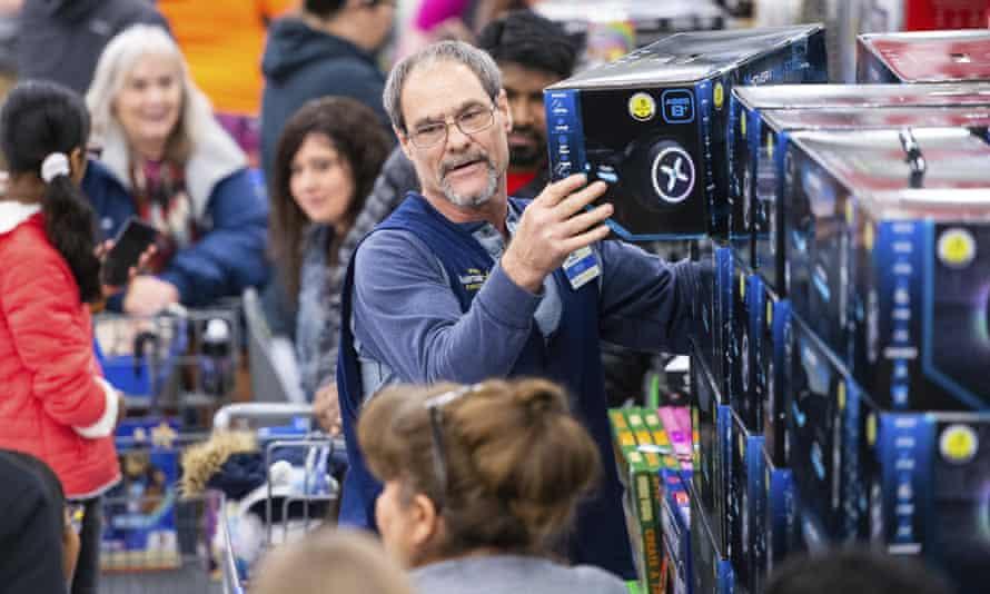 A Walmart associate helps customers shop Black Friday deals at the retailer's store event, on Thursday 28 November 2019, in Bentonville, Arkansas.