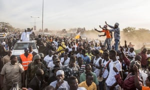 Young people celebrate President Adama Barrow's return to the Gambia