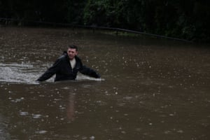 A man wades through a flooded street close to the Nepean River