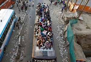 Migrant workers travel on a crowded bus as they return to their villages
