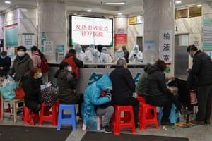 People wait in line on stools at Wuhan Red Cross Hospital