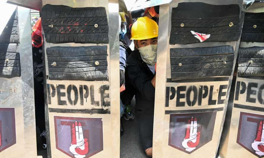 A protester looks on from behind shields during a demonstration against the military coup in Yangon on Sunday.
