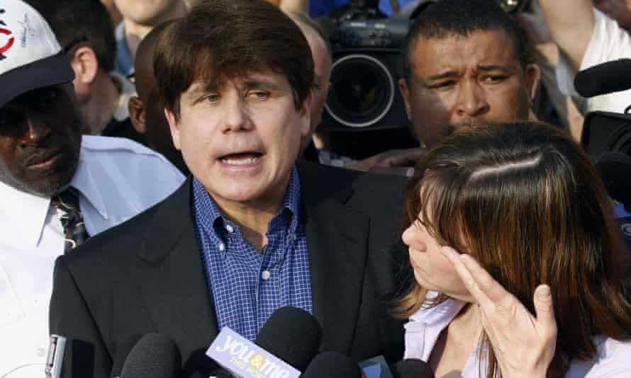 Former Illinois governor Rod Blagojevich speaks to the media outside his home in Chicago as his wife, Patti, wipes away tears a day before reporting to prison after his conviction on corruption charges in 2012.