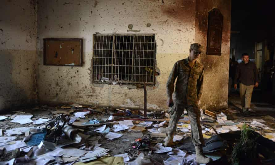 A Pakistani soldier walks in the debris of an army-run school after the attack by Taliban militants in Peshawar in December 2014