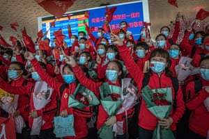Medical workers from the First Bethune hospital of Jilin University cheer during a ceremony at the airport as they prepare to leave the city