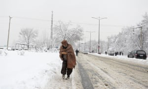 An Afghan man makes his way down a snow covered street in Kabul on Sunday