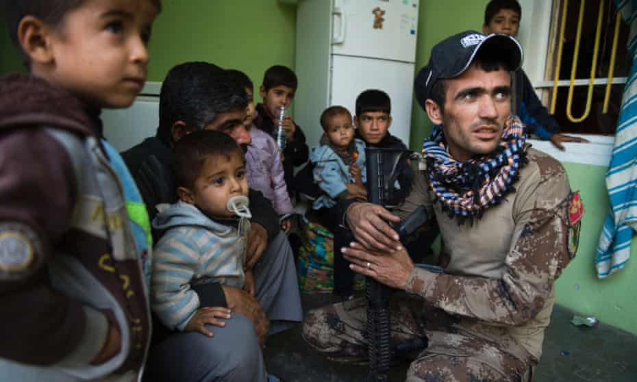 A soldier from the Iraqi special forces reassures members of a family who took shelter inside a building held by troops during fighting against Isis in 2016.