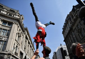 A protester in fancy dress performs acrobatics