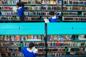High-school students browsing books in a library.