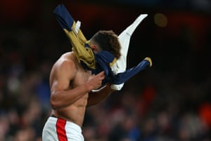Alex Oxlade-Chamberlain covers his face with a shirt as he leaves the pitch.