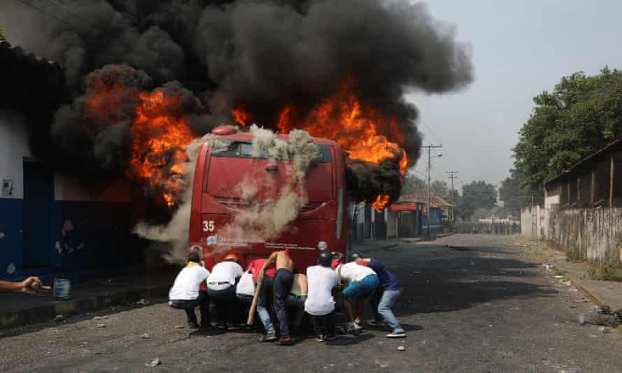 Demonstrators push a bus that was torched during clashes with the Bolivarian national guard in Ureña, Venezuela, on 23 February.