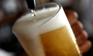 A pint of beer is poured into a glass in a bar