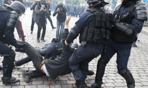 French riot police officers arrest a man in Paris.