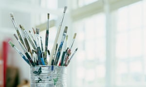 Paintbrushes in tin can on desk in classroom