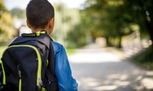 Teenage boy with school bag going home from school