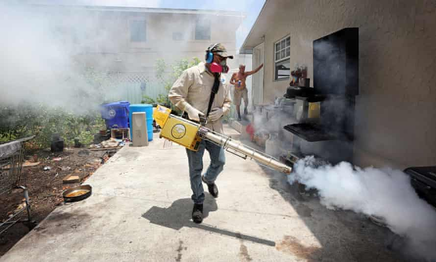 A Miami-Dade county mosquito inspector sprays around homes in the Wynwood area of Miami. Local mosquitos have infected 15 people with the Zika virus.