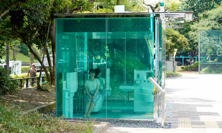 An employee of the Nippon Foundation demonstrates the transparent public toilet