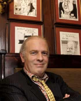 Martin Rowson sitting in front of his pen portraits at the Gay Hussar in 2007.
