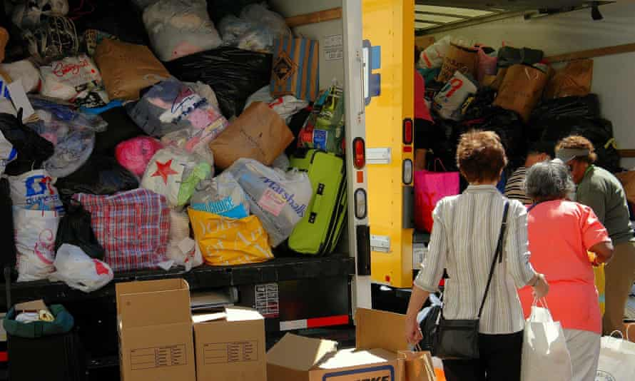 Women donate clothing that is piled into trucks at a relief drive for the victims of Hurricane Katrina