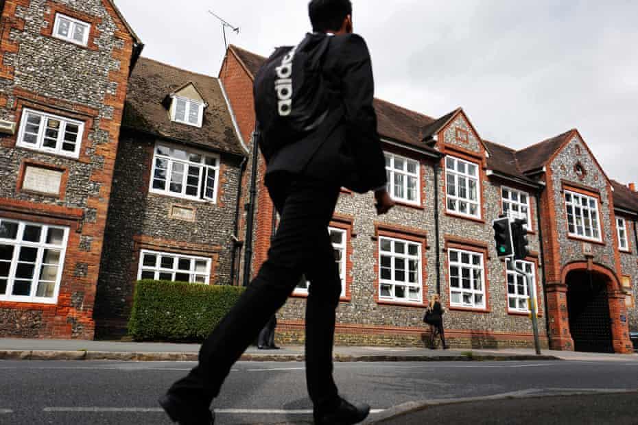 Boy in uniformwalking in front of Sir William Borlase's Grammar School