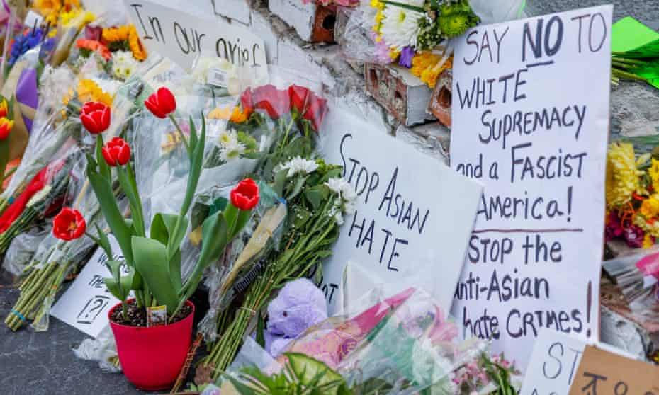 Flowers and signs at the growing memorial at the scene of two of the massage parlor shootings in Atlanta, Georgia, 19 March 2021.