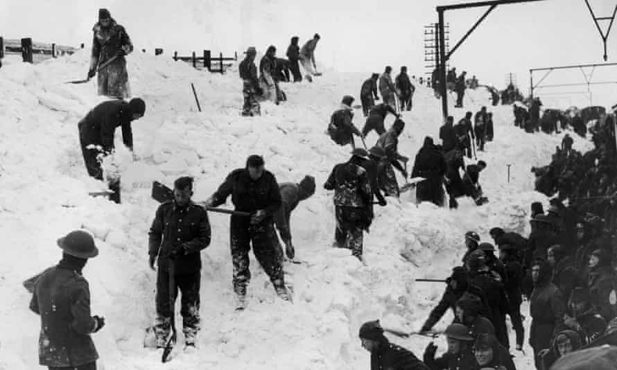 Soldiers dig out a snowbound train on the railway line between Manchester and Sheffield in 1940