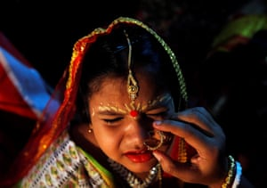 Kolkata, India. A young girl dressed as a kumari, or living goddess, winces as a nose ring is put on her in preparation for the Hindu festival of Durga Puja