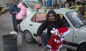 A vendor sells candy floss out of the back of a car in Bethlehem's Manger Square while a colleague sells Santa hats.