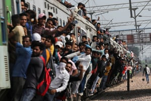 Passengers cling to a crowded train as it leaves a station in Ghaziabad, India