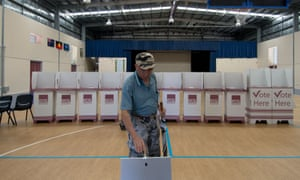 A voter casts his ballot after voting in the 2015 Queensland state election.