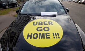A striking French taxi drivers displays the message, 'Uber Go Home' during a national protest about competition from private car ride firms.