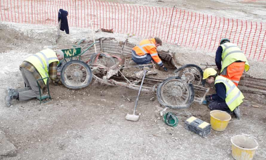 Archaeologists with the remains of a red MG sports car found at Larkhill.