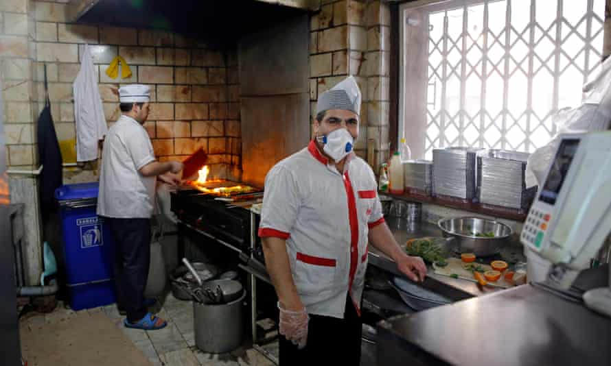 A chef works in a mask at a restaurant in Tehran