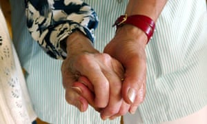 A care assistant holds an elderly lady's hand
