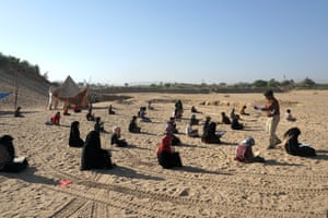 Pupils prepare for exams on the sand next to the displacement camp near Marib where they and their families have lived since fleeing fighting in northern Yemen, in December 2020.