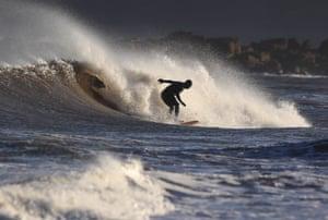Tyne and Wear, UKA surfer on Tynemouth beach on the North East coast