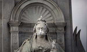 A statue of Queen Victoria in London wears a face mask put on by campaigners.